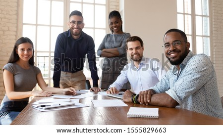 Happy successful multiracial business team gathered in modern boardroom for brainstorming working together on project posing look at camera teamwork representative of smart skilled specialists concept