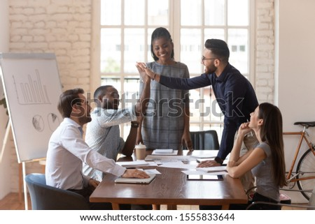 Arab and african colleagues giving high five feels satisfied, multiracial business people gather together in boardroom at group meeting, friendly gesture of support successful cooperation and loyalty #1555833644