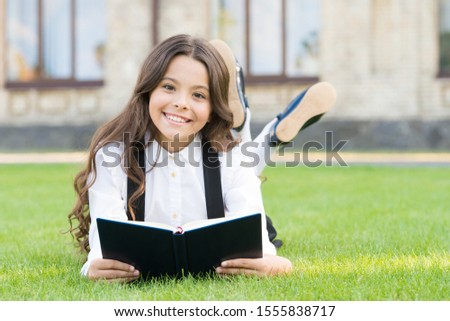 Her hobby is literature. Happy small child read childrens literature outdoor. Adorable little girl enjoy reading English literature at leisure. Learning foreign literature at school. #1555838717