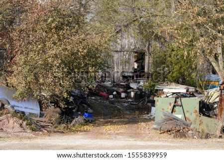 Junk heap in front of a barn on the side of the road  #1555839959