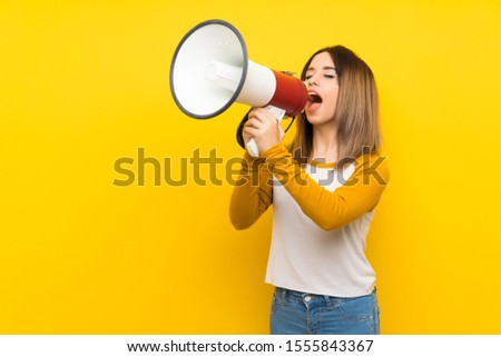 Pretty young woman over isolated yellow wall shouting through a megaphone #1555843367