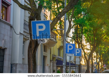 Parking or park sign for cars vehicles on trees and building background in the city. Traffic road road-sign. White letter P on a blue background. Sunny summer day. #1555843661