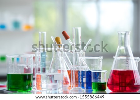 Chemical laboratory glassware with various colored liquids on table Royalty-Free Stock Photo #1555866449
