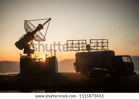 Creative artwork decoration. Silhouette of mobile air defence truck with radar antenna during sunset. Satellite dishes or radio antennas against evening sky. Selective focus Royalty-Free Stock Photo #1555873433