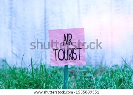 Conceptual hand writing showing Air Tourist. Business photo text process of going from place to place by any flying object Plain paper attached to stick and placed in the grassy land. #1555889351