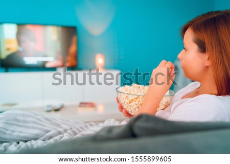 Young woman sitting on the bed sofa at home, lying with a popcorn bowl watching TV covered with blanket at her apartment alone enjoying movies or series #1555899605