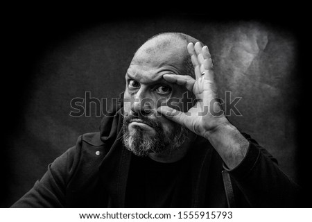 Black and white portrait of a bald bearded man in a hood on a dirty gray background looking at you. Close search concept. #1555915793