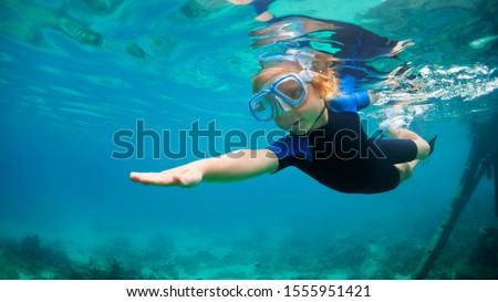 Happy little kid in snorkeling mask and wetsuit jump and dive underwater in coral reef sea lagoon. Family travel lifestyle in summer adventure camp. Swimming activities on beach vacation with child. #1555951421