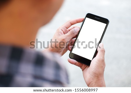 Cropped shot view of man hands holding smart phone with blank copy space screen for your text message or information content, female reading text message on cell telephone during in urban setting.  #1556008997