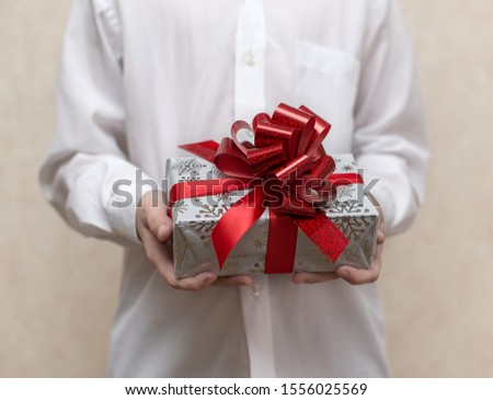 a child in a white shirt holds a gift in a box with a red bow #1556025569