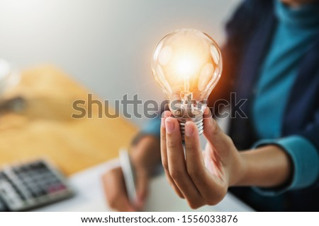 concept save energy power. businesswoman holding light bulb in office #1556033876