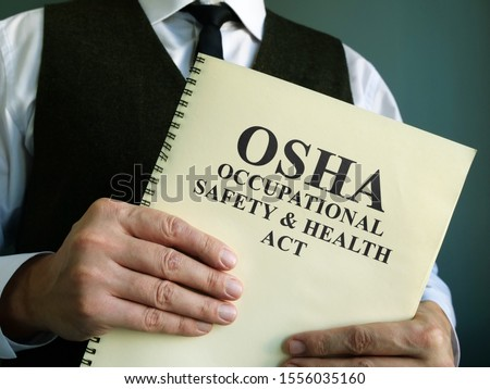 OSHA Occupational Safety & Health Act in the hands. #1556035160