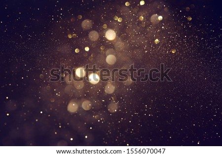 background of abstract glitter lights. gold and black. de focused #1556070047