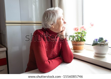 Old lonely woman sitting near the window at home. Concept of quarantine, coronavirus Covid-19. Danger for old people #1556085746