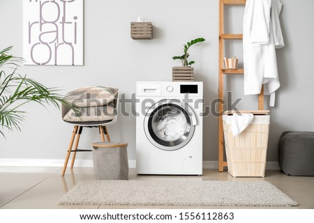 Interior of home laundry room with modern washing machine Royalty-Free Stock Photo #1556112863