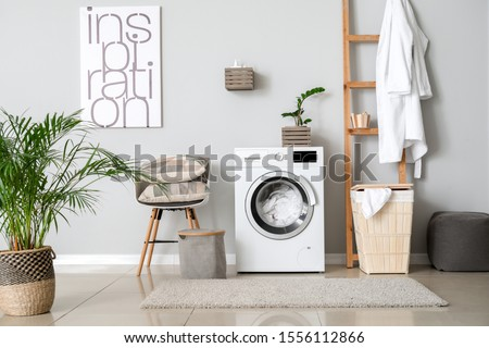 Interior of home laundry room with modern washing machine #1556112866