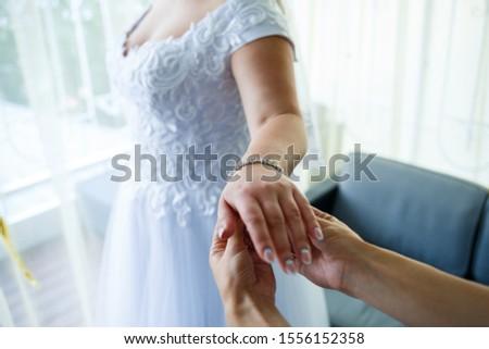 bride puts on wedding jewelry on the wedding day #1556152358