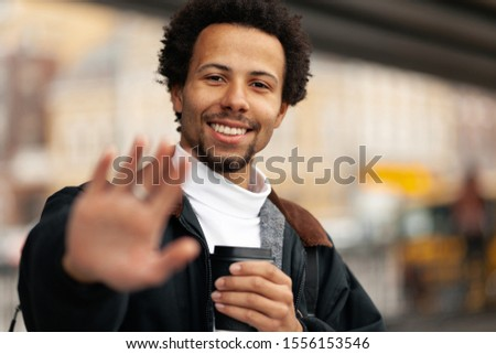 Portrait of African man with cup of coffee, raises his hand with gesture of greeting. #1556153546