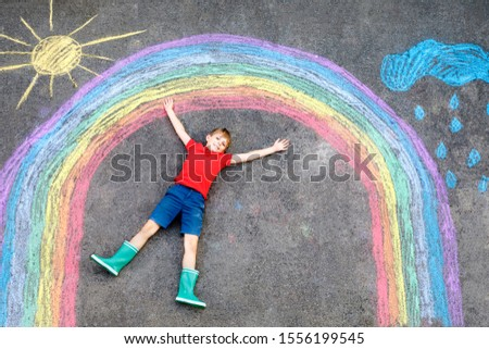 Happy kid boy in rubber boots with rainbow sun and clouds with rain drops painted with colorful chalks on ground or asphalt in summer. Creative leisure for children outdoors in summer