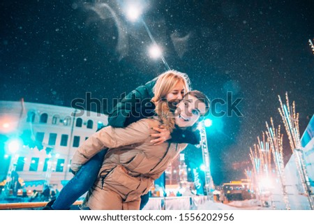 Cheerful and playful couple in warm winter outfits are fooling around #1556202956