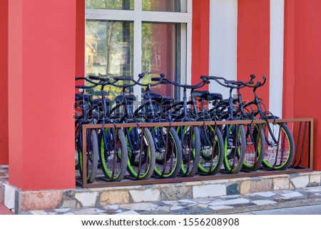 Parking identical bicycles near the building #1556208908