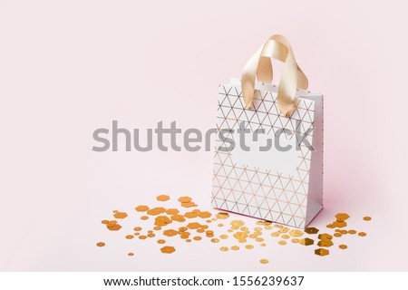 White Geometric shopping bag and trendy hexagonal sparkles on pink background. Holiday sale concept, isometric view. #1556239637