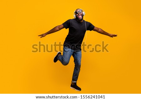 I believe can fly. Full size phtoo of funny positive afro american guy listen music with headset sing song raise hands like birds wings wear t-shirt sneakers isolated bright color background #1556241041