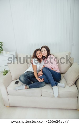 Two amazing girls sitting on the sofa, hugging one another, smiling lovely, looking at the camera. #1556245877