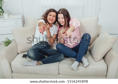 Joyful girlfriends are laughing desparately, pointing their fingers at the camera, sitting on the sofa in lotos position. #1556245898