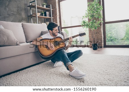 Photo of mixed race guy sitting floor leaning sofa hold acoustic instrumental guitar playing new written song sound signing creative talented person flat loft living room indoors #1556260190