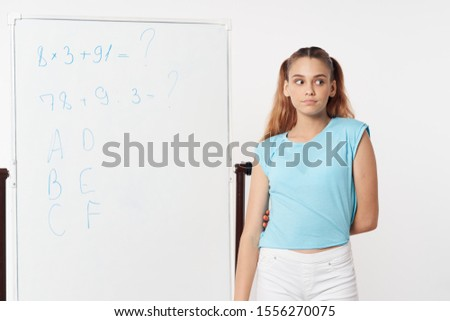 schoolgirl near the blackboard in the lesson and a blue tank top white pants #1556270075