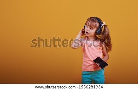 Portrait of cute little girl in headphones and with phone in the studio against yellow background. #1556281934