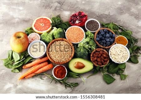 Healthy food clean eating selection: fruit, vegetable, seeds, superfood, cereals, leaf vegetable on background #1556308481