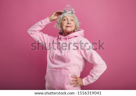 Picture of senior old woman with grey hair look straight. Stand alone and pose on camera. Hold crown or tiara on head with hand. Confident. Isolated on pink background