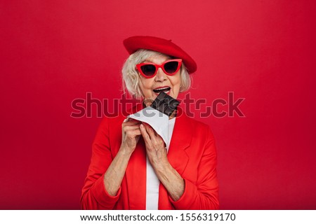 Positive old woamn in red clothes and beret stand alone and want to bite piece of chocolate bar. Tasty sweets. Milky or black chocolate bar. Stylish aged modern woman. Isolated over red background