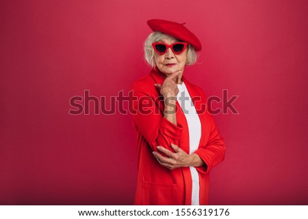 Almost full size picture of stylish fasion icon. Old woman in red coat and beret posing alone. Looking straight through sunglasses. Hold hand under chin. Isolated over red background