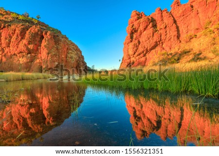 Scenic red rock formations of Glen Helen Gorge of West MacDonnell Ranges mirroring on calm waters of permanent waterhole in dry season at sunrise light. Northern Territory, Australian Outback. Royalty-Free Stock Photo #1556321351