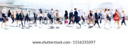 Walking people blur. Lots of people walking in the City of London. Wide panoramic view of people crossing the road.  Royalty-Free Stock Photo #1556335097
