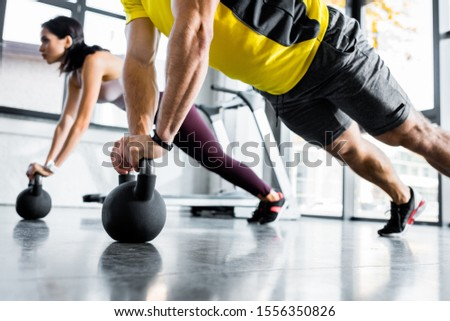 cropped view of sportsman and sportswoman doing plank on weights in sports center #1556350826