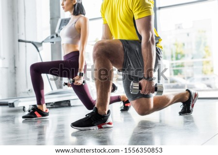cropped view of sportsman and sportswoman doing lunges with dumbbells in sports center #1556350853