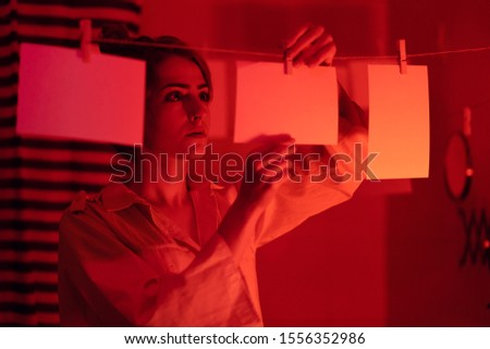 hobbyist or professional photographer. Young girl developing photos in a dark room. Retro style photography
