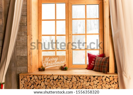 Cozy and frost winter day: christmas decoration on wood windowsill and snow landscape from outside. #1556358320