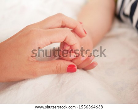 Mom holds the hand of a newborn baby. Close-up. A place to write. Placing text. defocusing. Baby's hand holding finger to mom. #1556364638