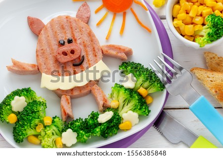 Fun Food for Kids - cute smiling ballerina pig made of a ham hamburger garnished with with broccoli florets,  sweet corn and cheese flowers. Healthy dinner for children concept #1556385848