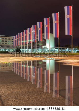 Flags of Serbia reflecting in the puddle of water at night, in front of the Palace of Serbia building, seat of several ministries of the government of Serbia in Belgrade, capital of Serbia #1556386181