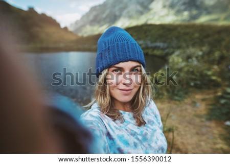 Woman hiker taking selfie photo using smartphone while hiking. Woman hiker wearing winter hat taking selfie picture