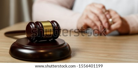 Hands of wife, husband signing decree of divorce, dissolution, canceling marriage, legal separation documents, filing divorce papers or premarital agreement prepared by lawyer. Wedding ring #1556401199