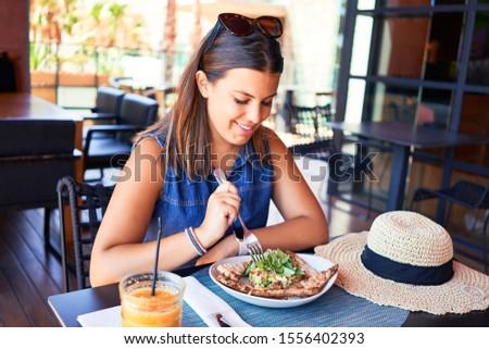 Young beautiful woman sitting at restaurant enjoying summer vacation eating delicious food #1556402393