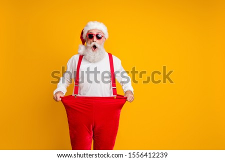 Portrait of crazy funky white bearded grandfather in santa claus hat hold big size trousers lose weight belly x-mas time show dieting effect  isolated yellow color background #1556412239