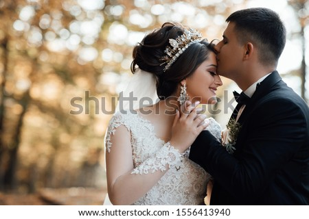 Happy bride and groom on their wedding. The groom kisses the forehead of the bride. Portrait of the bride. Newlyweds in the park. Happy couple. Wedding photo. Couple in love. Autumn wedding #1556413940